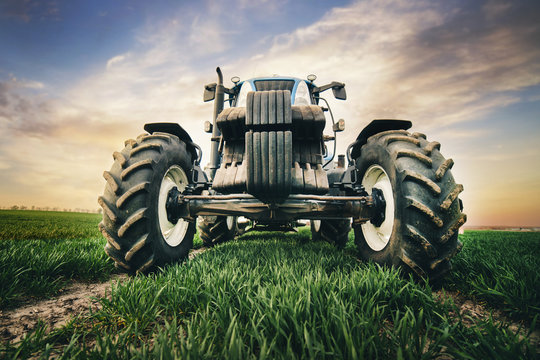 professional tractor with big tires is moving along the road in the field in the spring