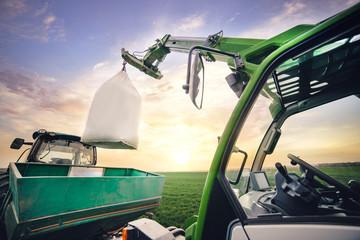 Fototapete - crane puts sack with fertilizer on trailer in field in spring