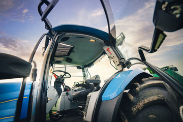 Wall Mural - open cab of driver of the tractor stands in the field in the spring