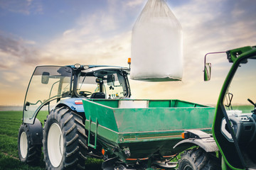 Fototapete - driver puts a sack of fertilizers on a square tractor trailer in the field in the spring
