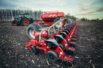 Fototapete - sowing machines stand on the ground in the field in the spring near the tractor
