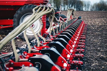 Wall Mural - sowing equipment stands on the ground against a tractor background in a field in the spring