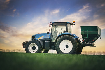 Fototapete - tractor with a trailer is driving by field for soil fertilization work in the spring