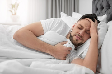 Man suffering from headache while lying on bed at home