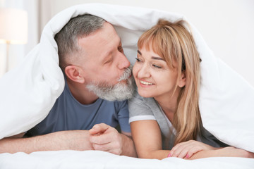 Mature couple together under blanket in bed at home