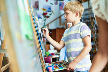 Side view portrait of cute  boy painting on easel during art class, concentrating on his masterpiece