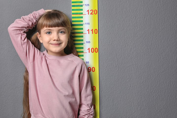 Little girl measuring her height on grey background