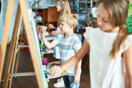 Side view at group of  children painting on easels during art class studio, pretty focus on little boy
