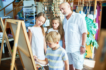 Portrait of mature art teacher teaching children painting in art class in cozy studio, copy space
