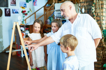 Side view portrait of senior art teacher teaching group of children painting in art class explaining techniques and pointing at easel