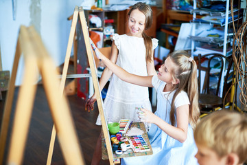 Portrait of pretty girl painting picture on easel in art class, with other children watching her, copy space
