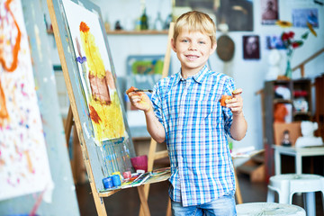 Portrait of smiling little boy painting on easel in art studio and posing, looking at camera, holding brush and paint, copy space