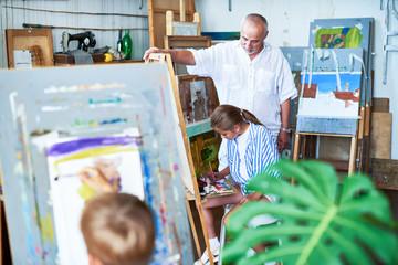 Portrait of senior  art teacher watching children painting during art class in school