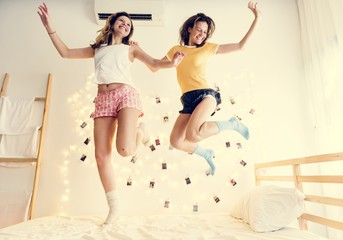 Two Caucasian women jumping on the bed together