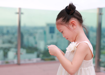 Portrait little Asian child girl in cream dress hold and looking photo in her hands at the rooftop of building.