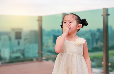 Cute little child girl in dress with using hands close her mouth at the rooftop of building.