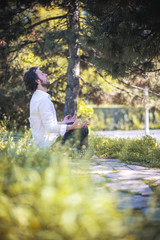 Young man practicing meditation and yoga focusing on a bright sunny day in a park surrounded by tall grass, serene and calm