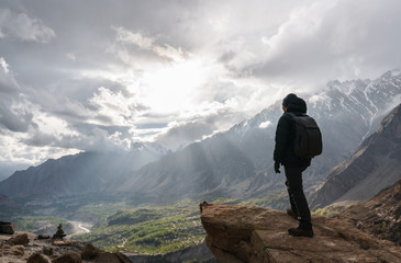 a man with backpack standing on mountain peak and bright sunlight through cloudy sky. Travel lifestyle and achievement success concept