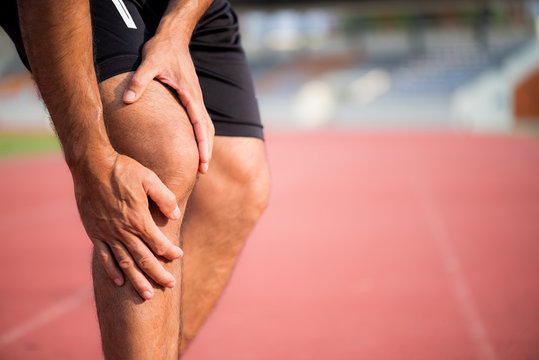 young sport man with strong athletic legs holding knee with his hands in pain after suffering muscle injury during a running workout training on Running Track. Healthcare and sport concept.