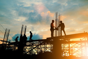 Silhouette of engineer and construction team working at site over blurred background sunset pastel for industry background with Light fair. Wall mural