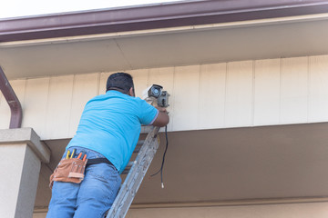 Vintage tone rear view of technician installing surveillance camera on roof. Latino handyman on ladder with tool belt  installing CCTV