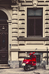 Red vintage scooter parked on a sidewalk
