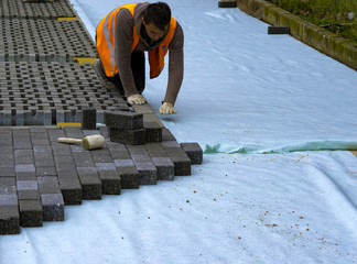 Construction worker laying interlocking paving concrete onto sheet nonwoven bedding sand and fitting them into place.