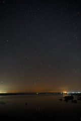 Bright stars of the night sky against the background of the smooth surface of the lake.