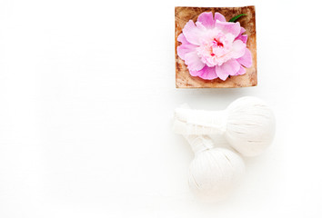 Herbal Thai massage balls and flower in a bowl with water. Spa concept. Flat lay