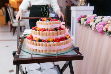 waiter will present at the restaurant. Wedding cake with berries. Bride and groom cut sweet cake on banquet in restaurant.