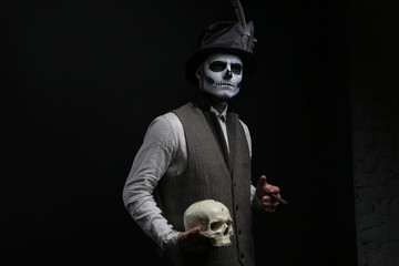 Guy in a makeup with a cigarette and a skull