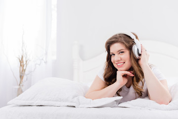 young smiling woman in pajama listening music in headphones on bed at home