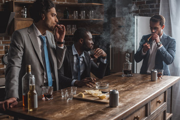 young multiethnic businessmen smoking cigars and drinking alcohol while partying together