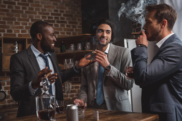 smiling multiethnic male friends in suits talking, drinking whiskey and smoking cigars