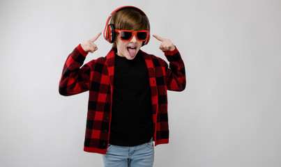 Cute confident little caucasian boy in checkered shirt in sunglasses fooling listening to music in headphones on grey background