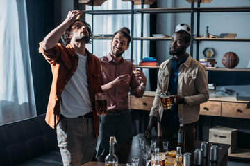 young multiethnic male friends drinking beer and partying together