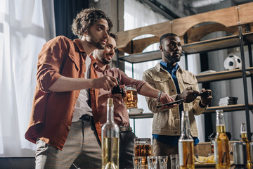low angle view of multiethnic men playing with joysticks and drinking beer together