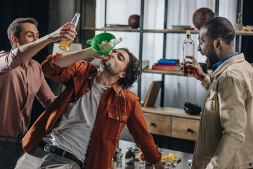 Poster de jardin Bar drunk male friends drinking alcohol beverages from funnel at party