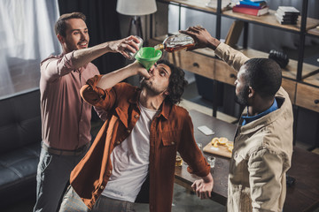 Poster de jardin Bar high angle view of man drinking from funnel while friends pouring alcohol beverages from glass bottle and can