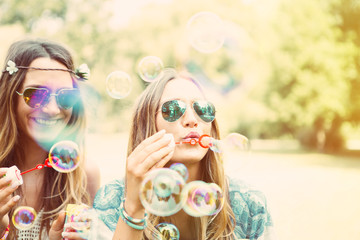 freundinnen machen seifenblasen in einem park. zwillinge