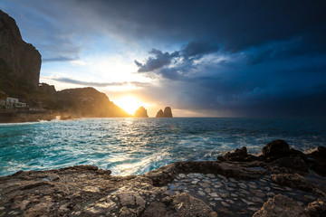 Spectacular cloudy sunrise view of Faraglioni rock