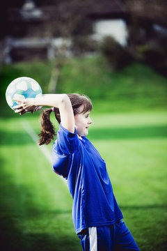 Teen girl playing soccer at local stadium outside on grass field making throw-in with the ball. Children playing football. Favourite sport, football fever worldwide.
