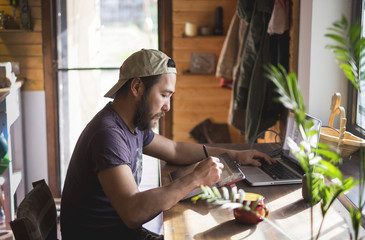asian man with beard working on a tablet and a laptop at home