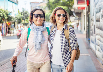 Stylish and beautiful mature mother and adult daughter are walking along the street. Family, travel, shopping, joy, communication
