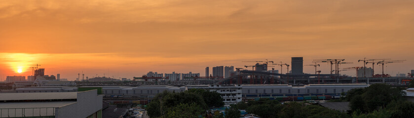 panorama of sunset in cityscape and construction site