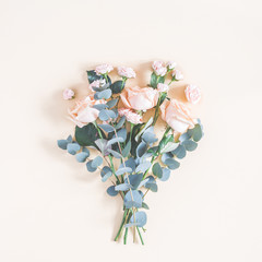 Flowers composition. Bouquet made of rose flowers and eucalyptus branches on pastel yellow...