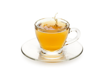 Fototapete - tea in glass cup with drop splashing, on white background