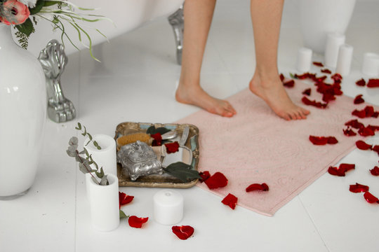 Bath mat. Legs on the rug after the bath. Rose petals and candles.