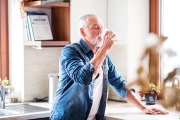 Senior man drinking water in the kitchen.