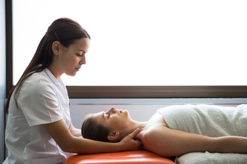 Side view of beautiful woman in medical overall tending female patient during physiotherapy session.